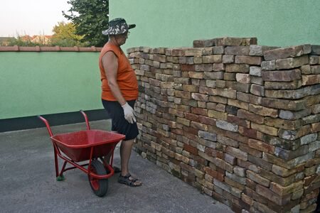 An elderly gentleman chooses a brick from a complex pile that he will carry with a cart