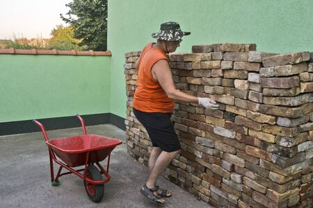 An elderly gentleman with a hat chooses a brick from a complex pile that he will carry with a cart. Stok Fotoğraf
