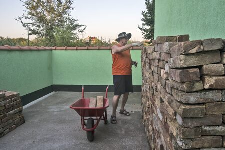 An elderly gentleman chooses a brick from a complex pile that he will carry with a cart.