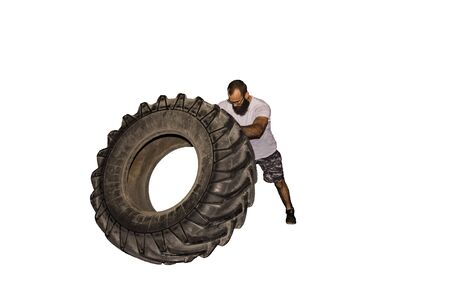 A man is engaged in fitness, spinning a large wheel from a tractor against a white background.