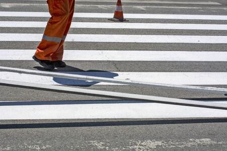 Workers are painting a pedestrian crossing in a city street.