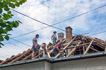 Zrenjanin, Serbia, July 22, 2020. A group of masters is working on the roof of a private house to replace an old tile. They use a nice day and stable weather without rain. They are disturbed by various cables that run over the roof of the house.