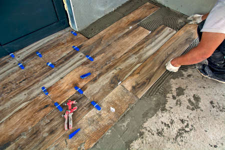 The master precisely glues new floor tiles. The panels look like laminate. Archivio Fotografico