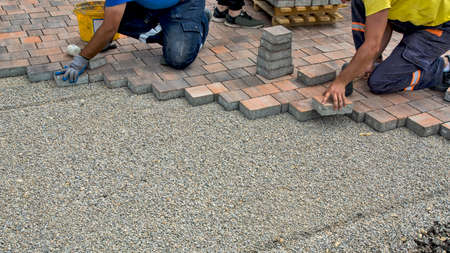 Master lay and install floor bricks on a public surface. The base is small stone and they fit concrete decorative pieces of brick.