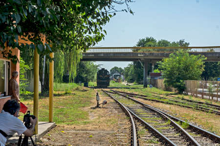 Zrenjanin,Serbia,August 31,2020.Diesel locomotives 661-243 of Serbian railways leave the station and pass under the overpass.Photographer and a railroad officer are waiting for the locomotive to pass. Éditoriale