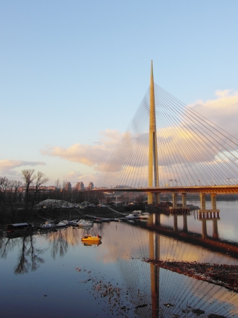 Cable bridge and boats underneath at sunset Stock Photo