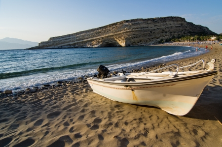 Boat resting on the sands of Matala beach at sunset