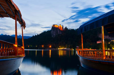Silent evening, boats on the calm lake and the old castle above the lake