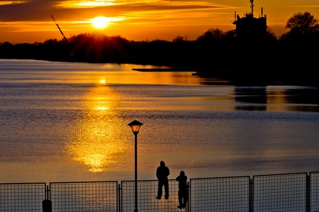 observers: Observers on a fence watching the sunset on Ada lake Stock Photo