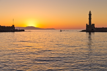 Little fishing sail boat passing the entrance to Hanja harbour at sunset. Hanja is one of the oldest cities and harbours at the island of Crete photo