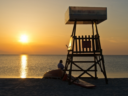 Lifeguard watchtower at sunset on the beach in Greece photo