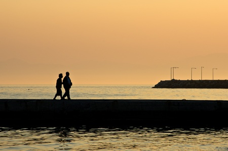 Grandpa and grandma walking by the sea at sunset in Greece