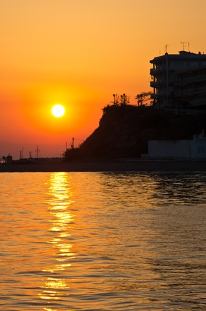 Hotel by the sea at sunset in Greece photo
