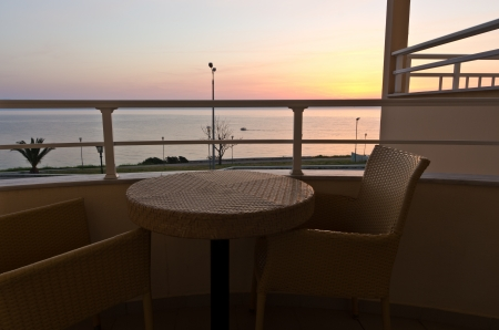 Table and two chairs on a balcony by the sea at sunrise in Greece photo