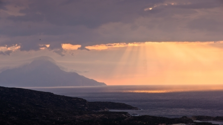 Divine light, stormy sky and sunrise on a landscape around holy mountain Athos in Greece photo