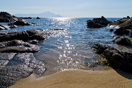 Rocks and sand of a beautifull beach in Greece, holy mountain Athos is in background