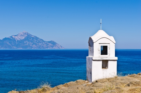 Small white church or chapel with holy mountain Athos in background, Greece photo