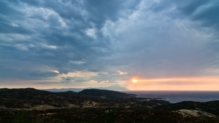 Stormy sky, sunrise at sea and landscape around holy mountain Athos in Greece photo