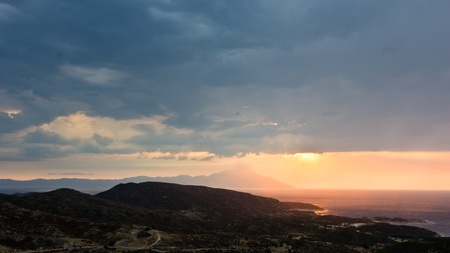 Stormy sky, sunrise at sea and sun rays on a landscape around holy mountain Athos in Greece photo