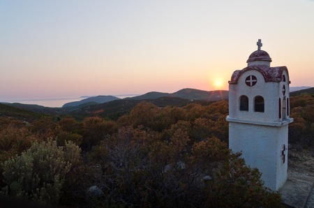 Small church or chapel with typical Greek landscape at sunset, Sithonia, Greece photo