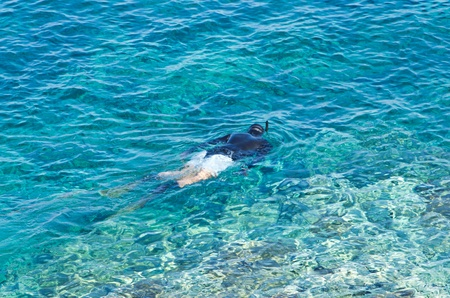 Diver or snorkler at Aegean sea near small greek island, Macedonia, Greece photo