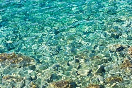 Rocky sea floor visible thru crystal clear turqoise water of Aegean sea in Greece