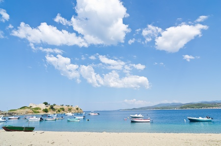 Under the perfect clouds, boats in a small fishing harbour by the beach in greece photo