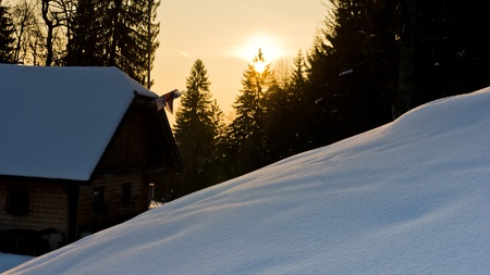 Sunrise reflections on a snow in front of mountaineer house at slovenian alps