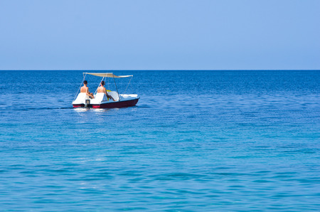 Couple driving a pedal boat on a vacation at Aegean sea somewhere in Greece photo
