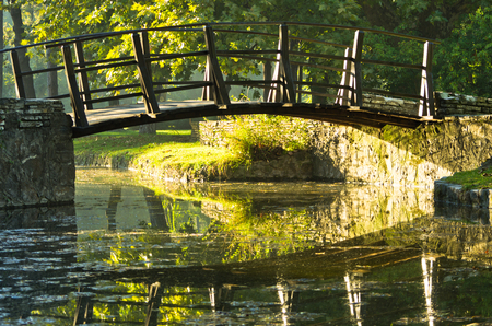 Little wooden bridge on first sunrays at morning in Topcider park photo