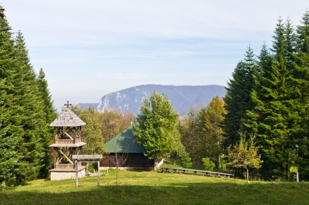 serbia landscape: Viewpoint on a landscape of mount Bobija, meadow in front of an old wooden church surrounded by tall fir trees with rocky peaks in backgound, west Serbia Stock Photo