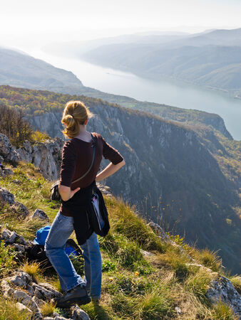 Girl taking a rest at the top of a 2000 feet vertical cliff over the Danube river at Djerdap gorge, east Serbia photo