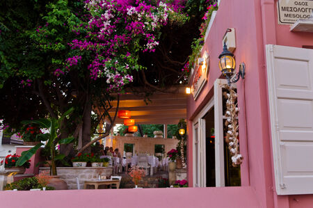 Restaurant garden at the street of old medieval city and harbor Rethymno, Crete, Greece