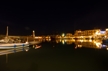rethymno: Ships and boats at the old venetian harbor with lighthouse at night, city of Rethymno, island of Crete, Greece Stock Photo