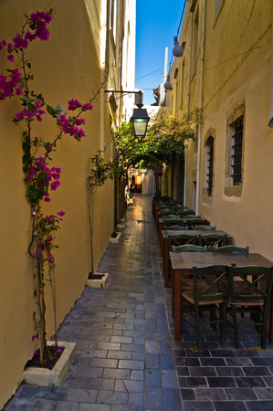 Restaurant in shade at the street of old medieval city and harbor Rethymno, Crete, Greece