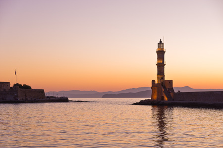 Scenic view of the entrance to Chania harbor with lighthouse at sunset, Crete, Greece