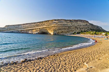 Matala beach and big rock with small caves, island of Crete photo