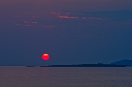 sithonia: Red sun and sunset at sea below small cape at Sithonia, Greece