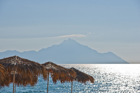 sithonia: Sunshades made from palm branches, aegean sea and a Holy mountain Athos in background, Sithonia, Greece Stock Photo