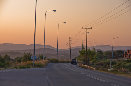 Typical greek coastal road at sunset with one pickup driving by, Sithonia, Greece photo