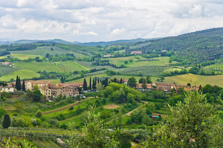Hills, vineyards and cypress trees, Tuscany landscape near San Gimignano, Italy photo