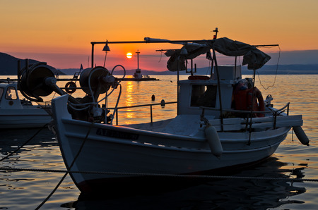 Fishing boats in Limenas harbour at sunset, island of Thassos, Greece photo