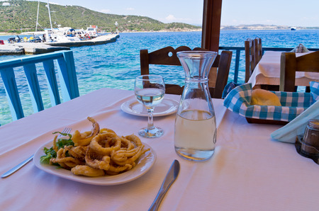 Eating fried squid and drinking white wine in a shade of a typical greek taverna by the harbour, Amoulani island, Greece Banco de Imagens