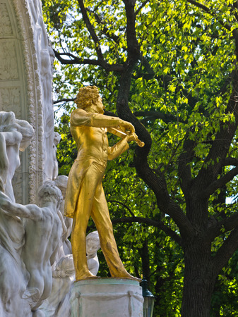 Golden statue of famous composer Johann Strauss at Stadtpark, downtown Vienna, Austria photo