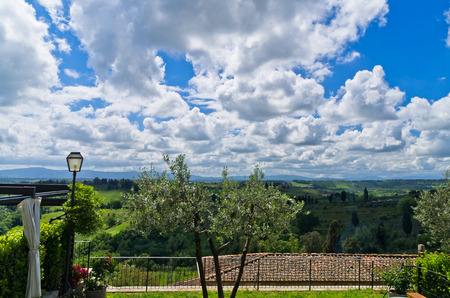 Hills, vineyards and cypress trees, Tuscany landscape from a restaurant terrace near San Gimignano, Italy photo