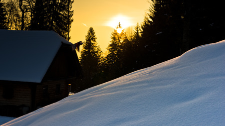 Sunrise reflections on a snow in front of mountain hut at slovenian alps near lake Bled photo