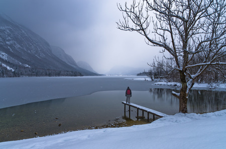 Watching the coming of a snow storm over frozen lake Bohinj in Slovenian Alps, Slovenia photo