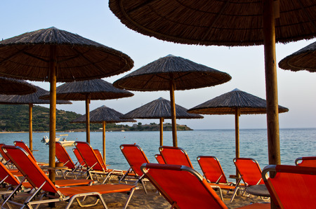 orange chairs: Orange chairs and stray parasols on a beach at sunset, west coast of Sithonia, Greece Stock Photo