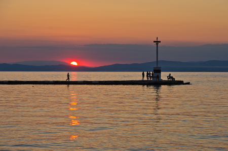 Lighthouse and pier in Limenas harbour at sunset, island of Thassos, Greece photo