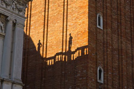 piazza san marco: Figurine shadows on a Campanila bell tower wall at piazza San Marco in Venice, Italy Stock Photo
